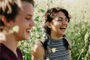 Two young adults laughing in a wheat field after receiving counseling for anxiety | Anxiety therapist | help for anxiety Psychologist in Baltimore | Anxiety Treatment with trained psychologists | New Connections Counseling Center | Baltimore, MD 21210