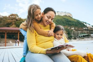 Young mother and two daughters reading a book outdoors | Therapy for women in Baltimore, MD with a women's therapist | Counseling for women | New Connections Counseling Center | Baltimore, MD