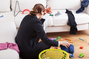 Woman sitting on the floor with hand on her head next to toys and a laundry basket | psychologist in Baltimore | Counseling for women in Baltimore, MD| Therapy for mothers | New Connections Counseling Center | Baltimore, MD 21210