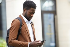 African American man in suit looking at his smart phone in Baltimore | Therapy for Anxiety | Anxiety Treatment | New Connections Counseling Center | men's therapy in Baltimore, MD 21210