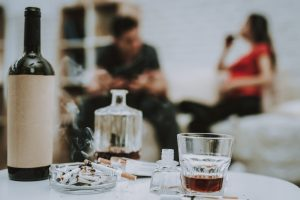 Two people drinking in the background and a whiskey decanter and glass on a table in the foreground representing alcohol abuse. Alcohol abuse treatment in Baltimore, MD for alcoholic adults dealing with Substance abuse needing treatment. New Connections Counseling Center can help in MD, 21210