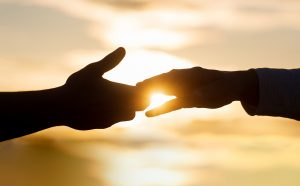Image of two hands touching with a sunset in the background. This image represents the support that people can receive when using anxiety treatment in Baltimore, MD to heal from racial injustice. | 21286 | 21093