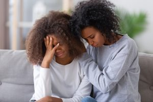 Image of a mother and daughter looking sad together on a couch. This image represents the impacts of racial injustice in Baltimore, MD on Black individuals. Working with an anxiety therapist in Baltimore, MD can help. | 21210 | 21212