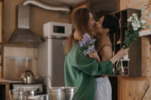 Image of a female/female couple hugging and smiling in their kitchen. Working through marriage counseling in Baltimore, MD can help couples discover their love for one another again.   21286   21093