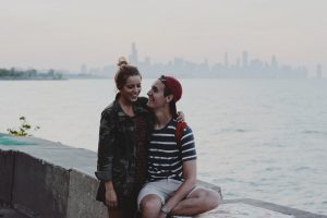 Image of a young man and woman in a relationship sitting by a lake in their city. The joyful looks on their faces illustrate the happiness one can find with their partner after working through couples therapy in Baltimore, MD together. | 21210 | 21212
