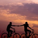 Photo of a male and female couple riding bikes together into the sunset and holding hands. They represent a couple that feels more connected than ever after going through couples therapy in Baltimore, MD. | 21286 | 21093