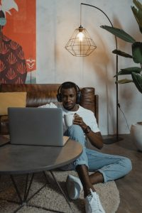 """Image of a man sitting on the living room floor and searching the web. This image illustrates how easy it is for people to look for """"online therapy in Maryland"""" on their computer and begin online counseling. 