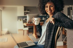 Image of a woman sitting on a chair with a laptop on her lap and a cup of coffee in her hand. She exemplifies what an individual using online therapy in Maryland may look like during a counseling session. | 21210 | 21212
