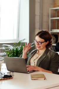 Image of a woman sitting at her desk working on a laptop and waving at someone on the screen. She illustrates what an online counseling session may look like for those looking for online therapy in Maryland. | 21209 | 21204