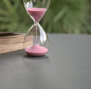 Image of a pink hour glass sitting on a table. This image illustrates that EMDR therapy in Baltimore, MD is a time commitment. However, working with an EMDR therapist in Baltimore, MD can be very helpful. | 21286 | 21093