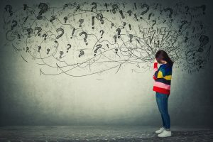 Image of a girl in a striped sweater with question marks illustrated around her head. Working with an EDMR therapist in Baltimore, MD can help answer questions you have about past trauma. | 21210 | 21212