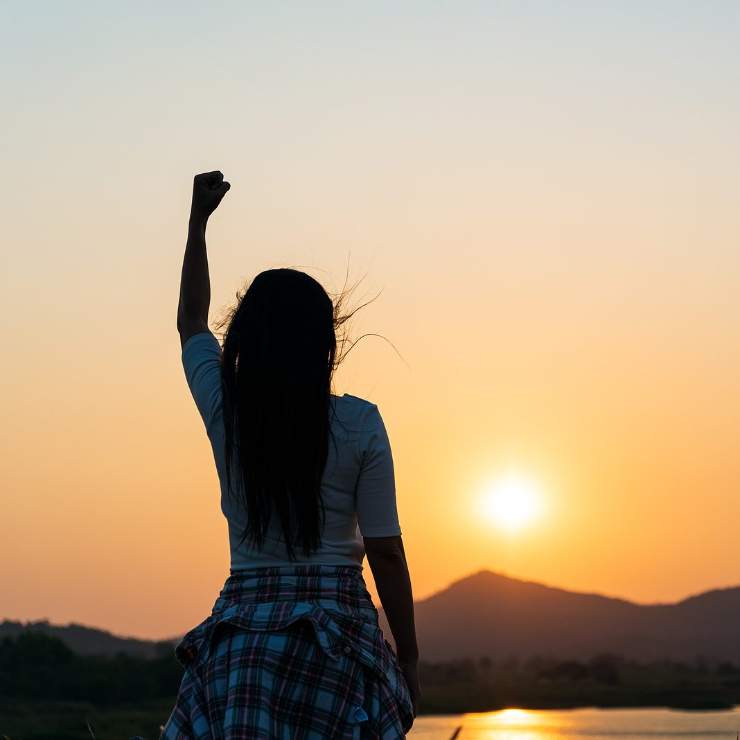 Image of a woman looking at a sunset with her fist held in the air. This image represents the confidence that you can feel after working with an EDMR therapist in Baltimore, MD. 21286 | 21093