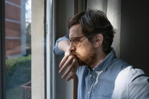 """Image of a man looking out the window with his hand on his mouth. He represents what someone experiencing trauma symptoms may look like. Those searching """"EDMR therapy near me"""" can find support from an EMDR therapist in Baltimore, MD. 21210 