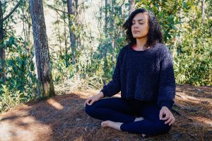Image of a woman sitting in the forest with her eyes closed meditating. She represents the peace you can find from working with an EMDR therapist in Baltimore, MD to treat trauma symptoms. | 21286 | 21093