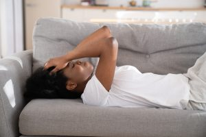 Image of a young woman sitting on a couch with her hands held to her forehead. The woman in this image depicts what someone struggling with symptoms of PTSD may look like. Someone with PTSD could seek help from a trauma therapist in Baltimore, MD. 21286 | 21093