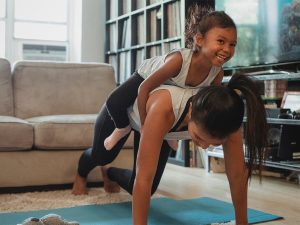 Single Mom doing push ups with her daughter on her back | New Connections Counseling Center, Baltimore, MD